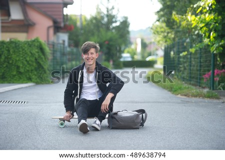 Teenager smiling and sitting on his longboard with his backpack near him with a suburban background.