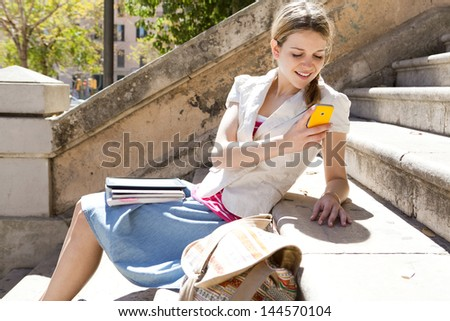 Teenager student using her smart phone while sitting down at a college stone steps during a sunny day, smiling. - stock photo
