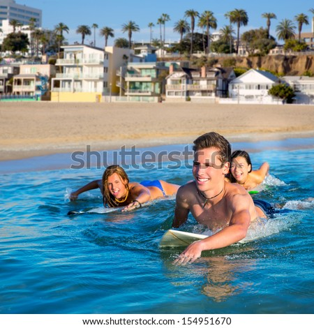 Teenager surfer group boys and girls swimming over the surfboard in santa monica california [photo-illustration] - stock photo
