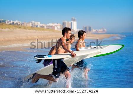 Teenager surfers surfing running jumping on surfboards at El Perello Cullera beach Spain - stock photo