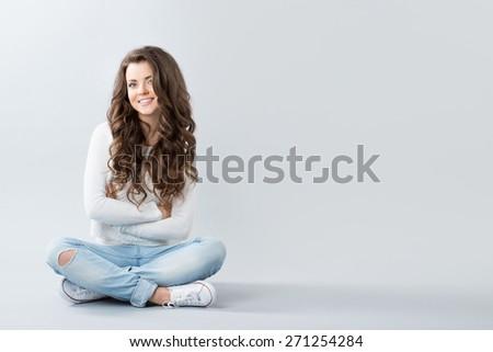 Teenager. Teenage Girl sitting. Girl with long wavy hair. - stock photo