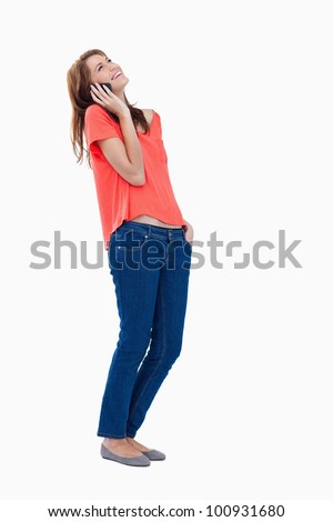 Teenager tilting her head while using her mobile phone - stock photo