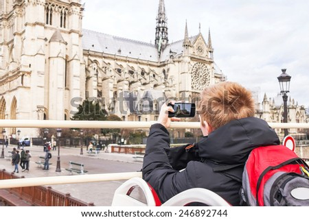 Teenager tourist is taking photo on cathedral of Notre Dame de Paris with mobile smart phone. Left-handed boy is on tourist bus. Caucasian male model. Travel, tourism, vacation concept. France. - stock photo