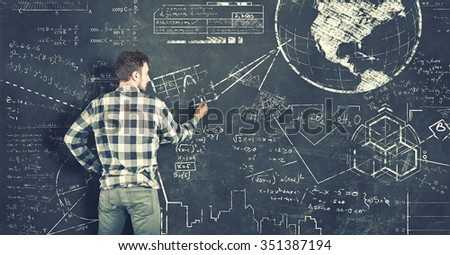 Teenager tries to solve problems on blackboard - stock photo