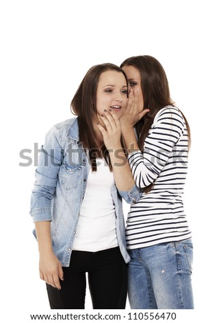 teenager whispering gossip to her sister on white background - stock photo