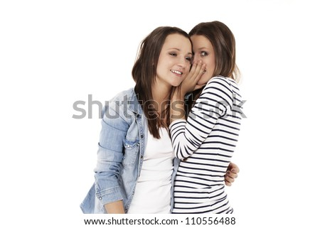 teenager whispering secrets to her friend on white background - stock photo