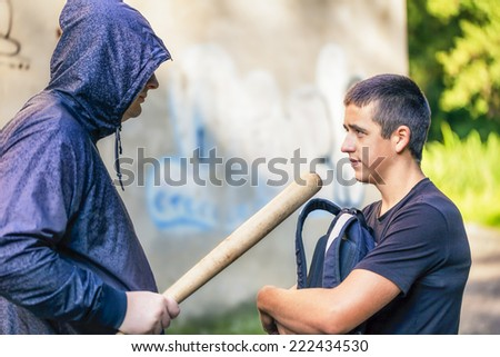 Teenager with a backpack against aggressive man at outdoor