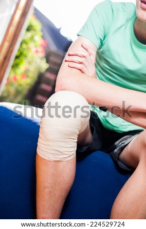 Teenager with a bandaged knee. - stock photo