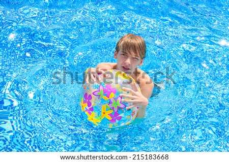 teenager with a beach ball in the water - stock photo