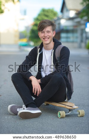 Teenager with backpack on a longboard.