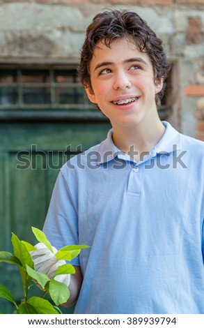 teenager with braces smiles while taking care of a lemon tree holding green leaves with latex gloves - stock photo