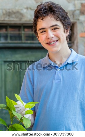 teenager with braces while taking care of a lemon tree holding green leaves with latex gloves - stock photo