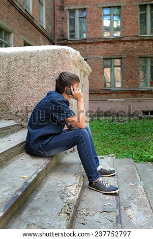 Teenager with Cellphone on the landing steps of the House