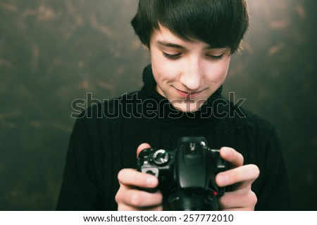 Teenager with digital compact camera - stock photo