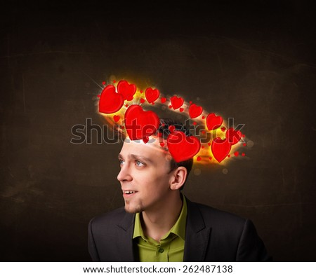 teenager with heart illustrations circleing around his head - stock photo