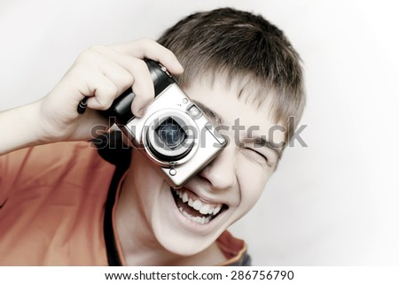 Teenager with Photo camera gets ready to take a photograph - stock photo