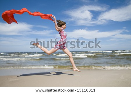 Teenager with red scarf on the beach