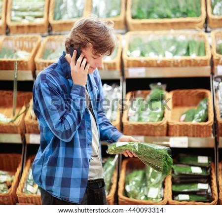 Teenager with smartphone choosing vegetables in a supermarket. - stock photo
