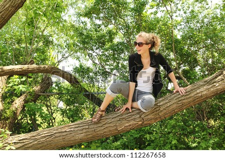 Teenager with sunglasses sit on a huge branch