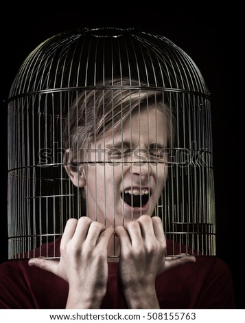 Teenager with the head inside a birdcage, concept