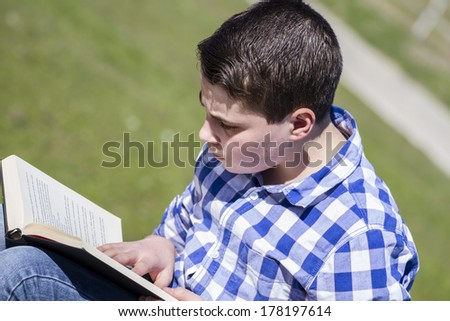 Teenager.Young man reading a book in outdoor with yellow apple.