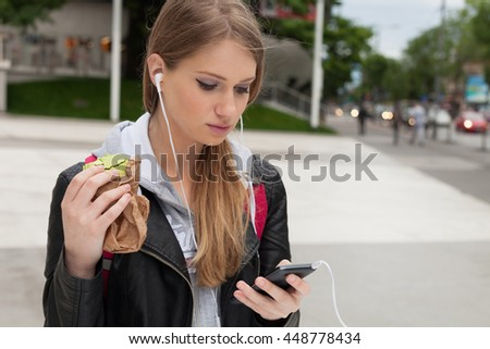 Teenager - young woman eating cakes in street and looking in phone - stock photo