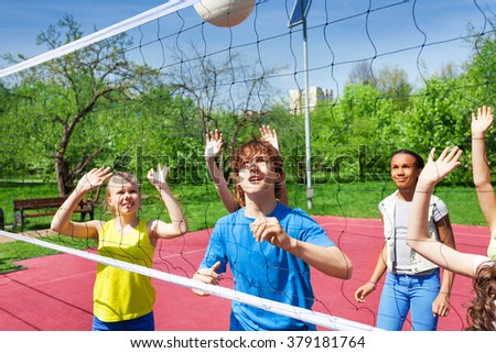 Teenagers are playing volleyball near the net - stock photo