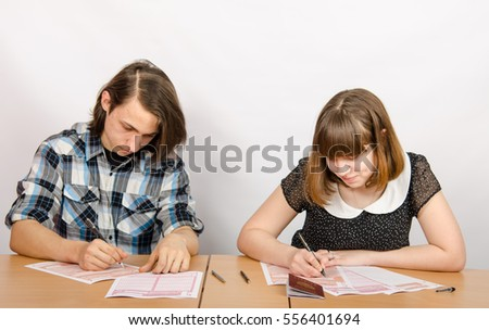 Teenagers at a table filled with the exam forms