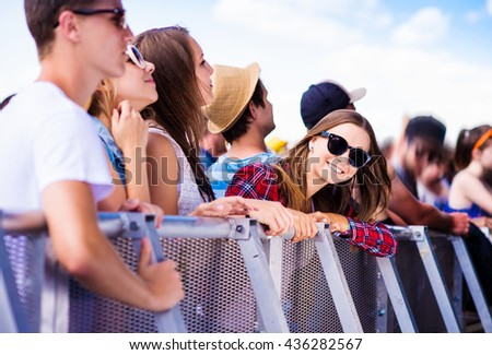 Teenagers at summer music festival, at the barrier