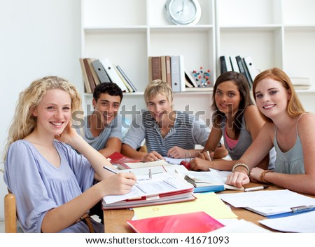 Teenagers doing homework in the library. Concept of education - stock photo