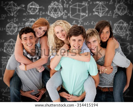 Teenagers giving their friends piggyback rides against black background - stock photo