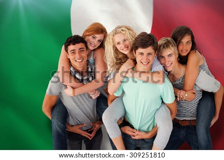 Teenagers giving their friends piggyback rides against digitally generated italian national flag - stock photo