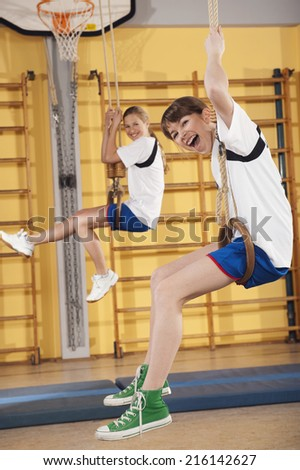 Teenagers hanging from flying rings in a gym