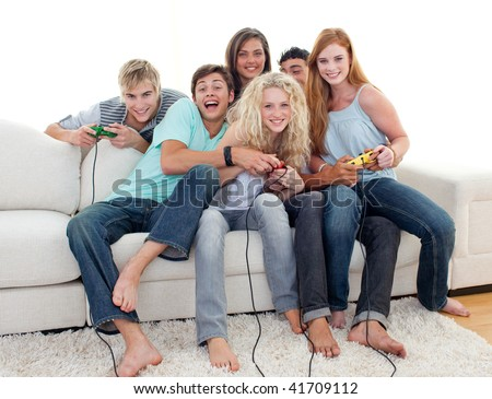 Teenagers having fun playing video games at home