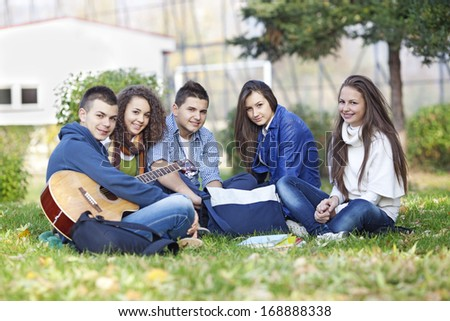 Teenagers having fun with guitar in the park after classes - stock photo