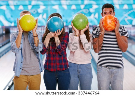 Teenagers hiding their faces behind bowling balls - stock photo