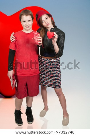 Teenagers holding a couple of Valentines Day hearts - stock photo