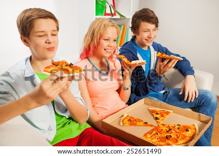 Teenagers holding pizza pieces and eating - stock photo