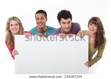Teenagers holding up a blank sign - stock photo