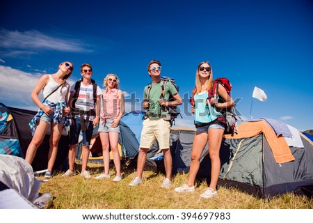 Teenagers in front of tents with backpacks, summer festival