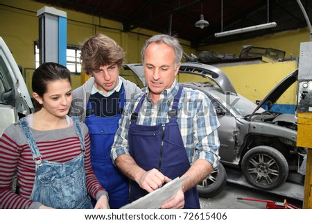 Teenagers in professional training with garage woner - stock photo