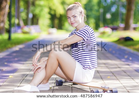 Teenagers Lifestyle, Concepts and Ideas. Positive Blond Caucasian Girl Posing With Longboard in Park Outdoors. Horizontal Shot