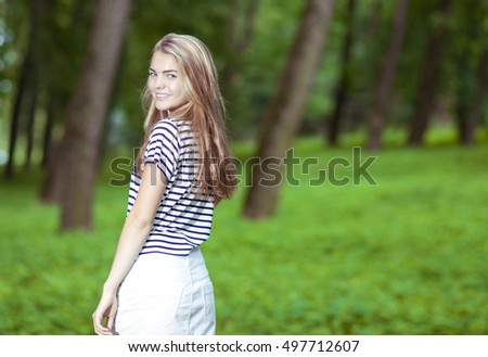 Teenagers Lifestyle Concepts. Portrait of Smiling Blond Caucasian Teenager Posing in Green Forest Outdoors.Horizontal Image Composition
