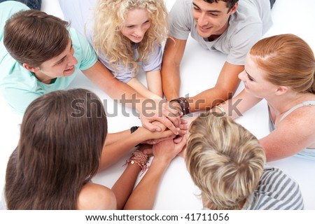 Teenagers lying on the floor in a circle playing hands games - stock photo