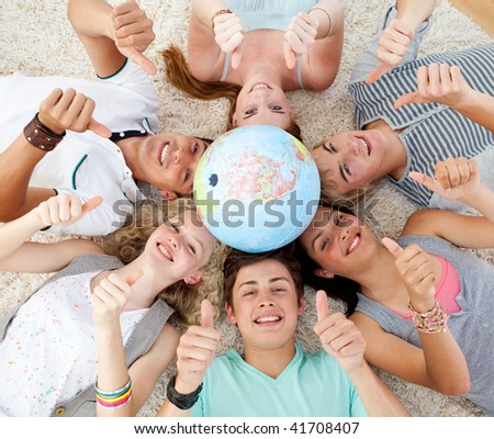 Teenagers on the floor with a terrestrial globe in the center of their heads and with thumbs up
