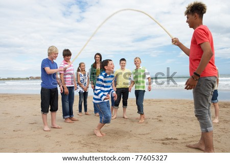 Teenagers playing skipping rope - stock photo