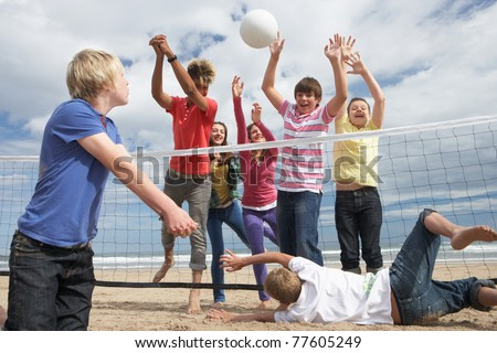Teenagers playing volleyball - stock photo