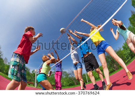 Teenagers playing volleyball on the game court - stock photo