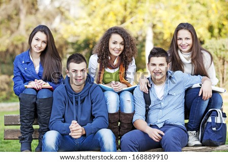 Teenagers resting in the park after classes - stock photo