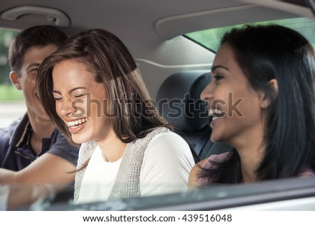 Teenagers riding in car - stock photo